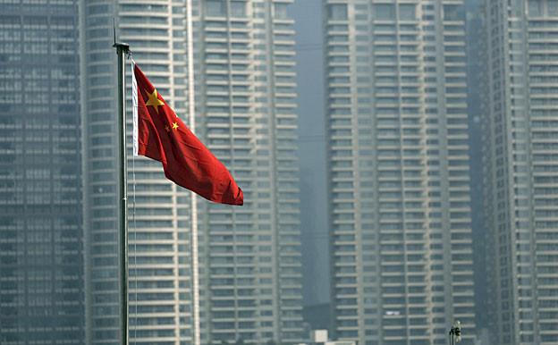 Eine chinesische Flagge weht vor den Hochhäusern in Shanghais Finanzdistrikt.