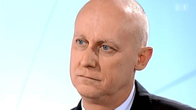 Daniel Thelesklaf in einem Fernsehinterview vor einem hellblauen Hintergrund.
