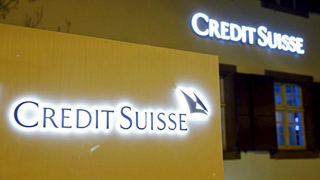 Das Logo von Credit Suisse leuchtet auf einer gelben Wand an der CS-Niederlassung in Riehen.