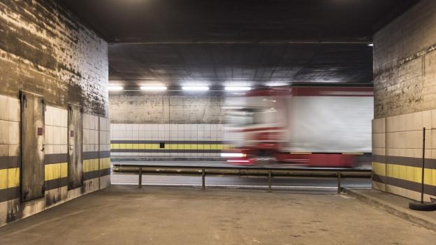 Im Gotthard-Tunnel fährt ein Lastwagen vorbei. Das Fahrzeug ist leicht verschwommen von der schnellen Bewegung.