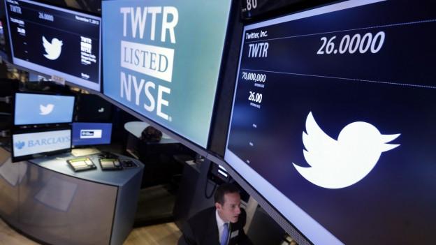 Aufnahme vom Parkett der Wallstreet. Auf Monitoren sind die Twitter-Logos zu sehen.