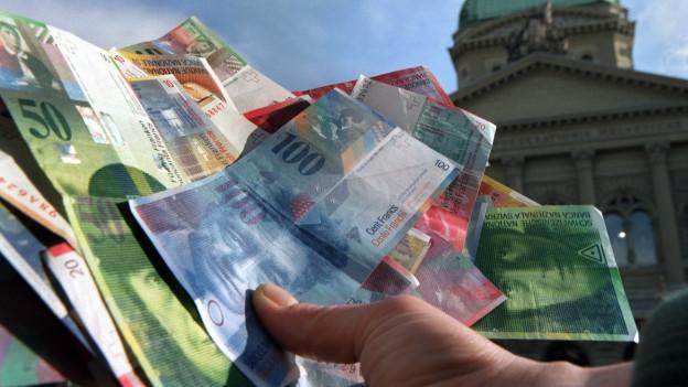 Eine Hand hält Geldscheine (im Hintergrund Bundeshaus).