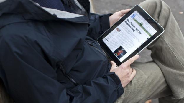 Aufnahme von einem Menschen (den Kopf sieht man nicht), der ein iPad auf den Knien hält. Die Seite von 20min ist erkennbar.