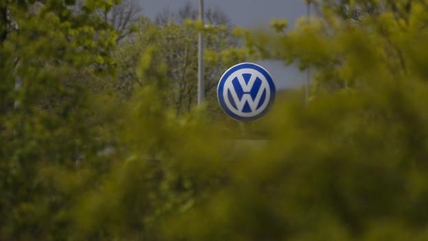 Ein VW logo in der Ferne, im Vordergund viele laubgrüne Bäume.