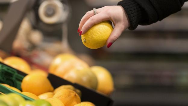 Eine Frau nimmt in einem Laden eine Orange aus dem Regal.
