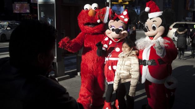 Elmo, Minnie Mouse und Mickey Mouse posieren mit Touristenmädchen. Links im Vordergrund: Umriss des fotografierenden Vaters.