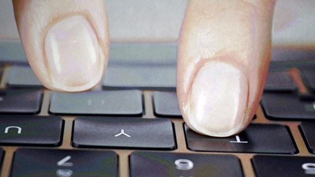 Zwei Finger schweben über einer Computertastatur.