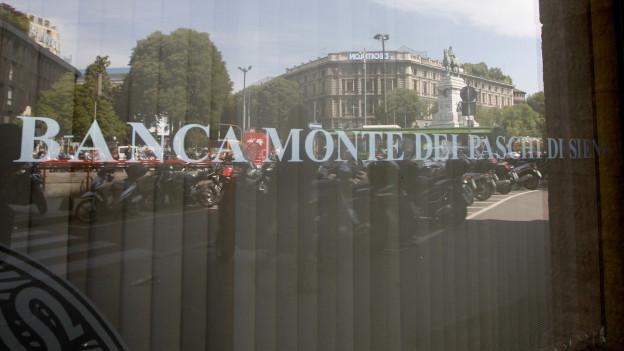Ein Fenster der italienischen Bank Monte dei Paschi mit dem entsprechenden Schriftzug, im Glas spiegelt sich die Umgebung.