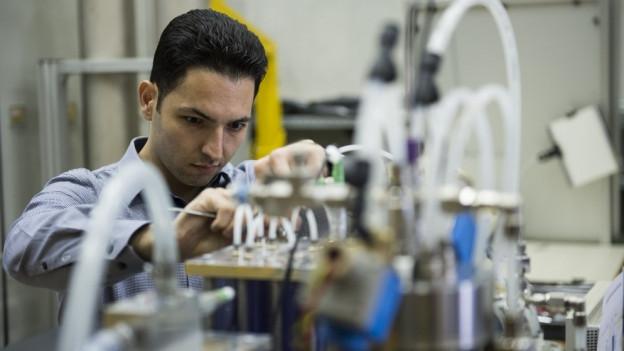 Ein Mann arbeitet an einer komplexen Apparatur.