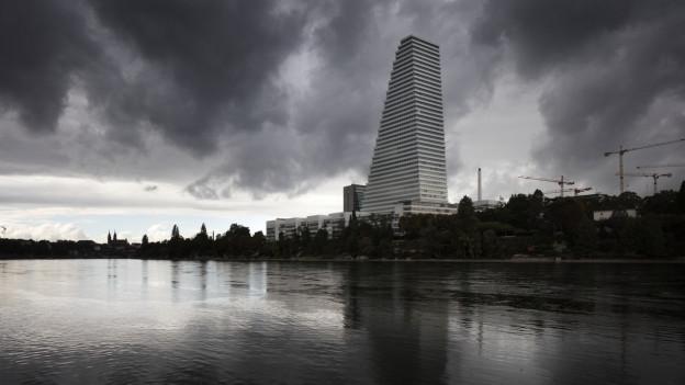 Der Rocheturme vom Rhein aus betrachtet, er spiegelt sich im Wasser, der Himmel ist grau und bewölkt.