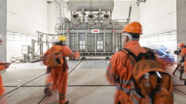 Im Inneren des Pumpspeicherkraftwerks Linthhal steht ein grosser Transformator: Eine Art grauer Container mit mehreren Behältern, Leitungen und Kondensatoren.