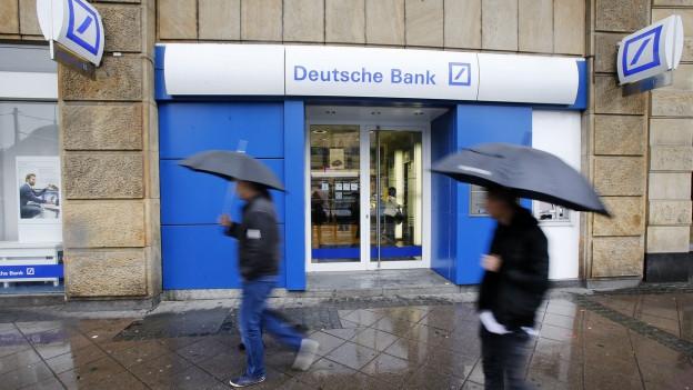 Eine Filiale der Deutschen Bank in Frankfurt am Main, es regnet, zwei Personen mit Regenschirmen gehen vorbei (27. April 2015).