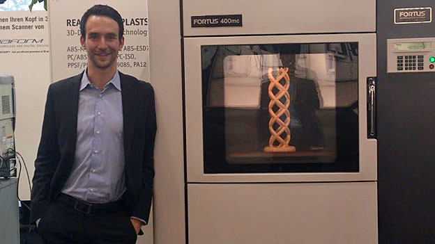 Matthias Baldinger steht vor einem 3D-Drucker.