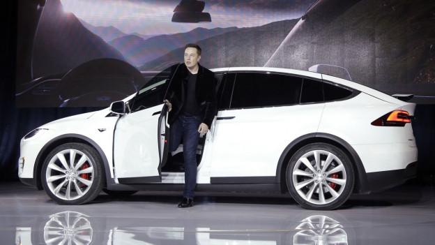 Tesla Gründer Elon Musk steigt aus einem weissen Tesla-Auto aus. Dieses steht auf einer Bühne anlässlich einer Präsentation.