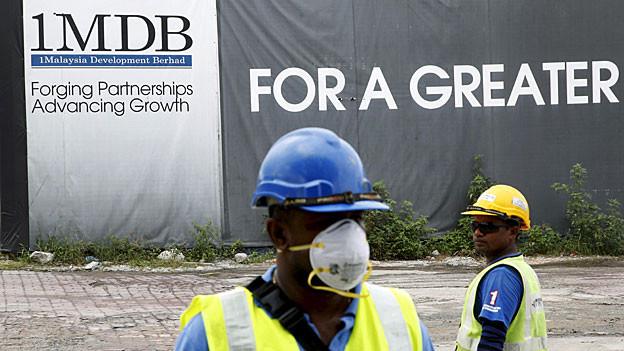 Bauarbeiter stehen vor einem Werbebanner, auf dem steht: «Forging Partnerships, Advancing Growth».