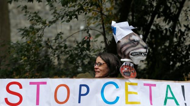 Bild einer Anti-CETA Kundgebung: Der Kopf einer Frau schaut über ein Transparent, auf dem «Stop CETA» zu lesen ist.