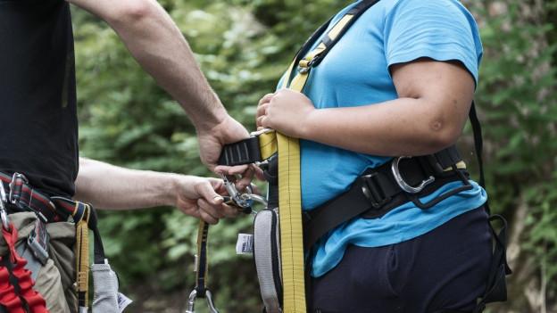Bild von einem übergewichtigen Menschen, der sich eine Kletterausrüstung anzieht. Der Kopf ist nicht zu sehen.