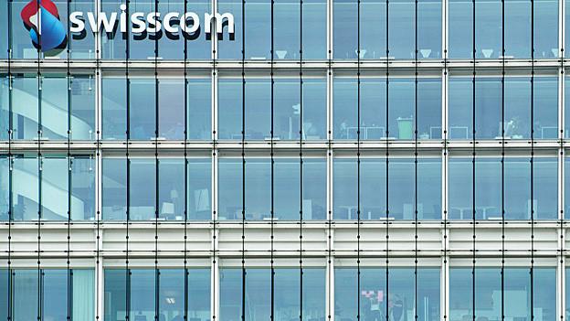 Das Logo von Swisscom an einem Glas-Gebäude.