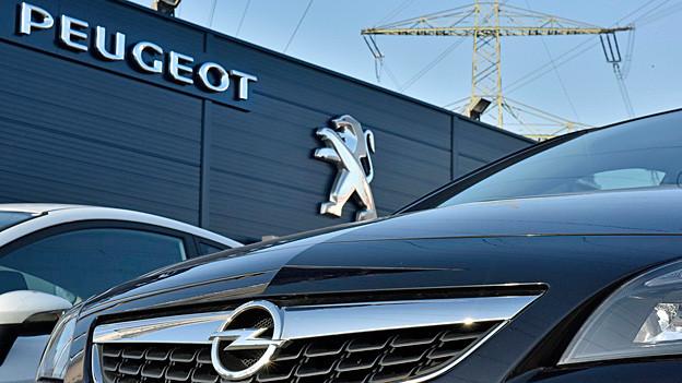 Ein Opel steht vor dem Laden eines Peugeot-Händlers.