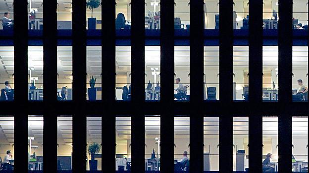 Beim Blick in ein Bürohaus der Credit Suisse, sieht man viele Angestellte an der Arbeit.
