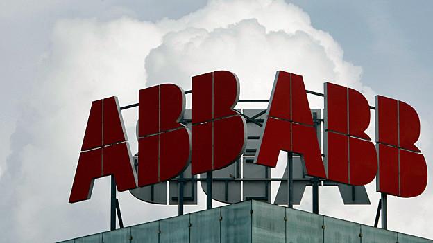 Hinter dem Logo von ABB türmen sich Wolken auf.