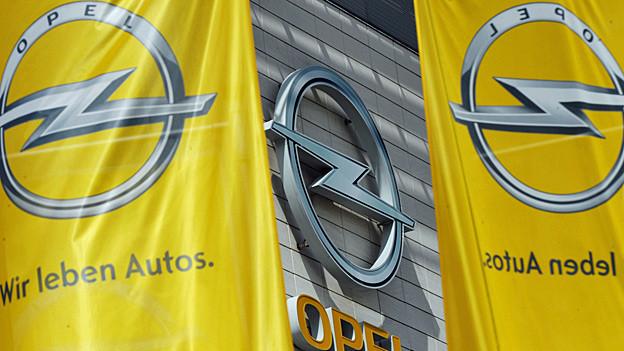 Unter dem Opel-Logo auf einer gelben Flagge steht: «Wir leben Autos».