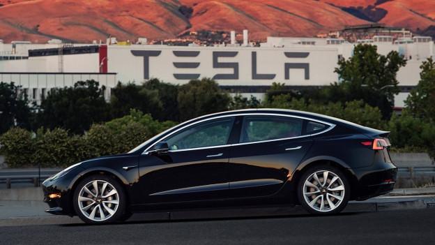 Auf dem Bild zu sehen ist der neue Tesla 3 vor dem Logo des Autobauers.