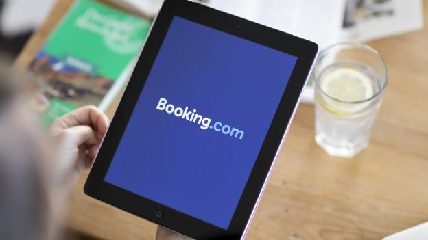 Eine Person besucht die Website des Online-Reisebüros Booking.com auf einem iPad
