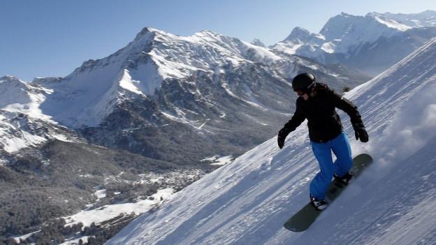 Eine Snowboarderi kurvt eine Piste runter.