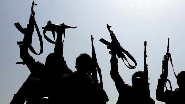 Vier Jemeniten halten ihre Gewehre in die Höhe.