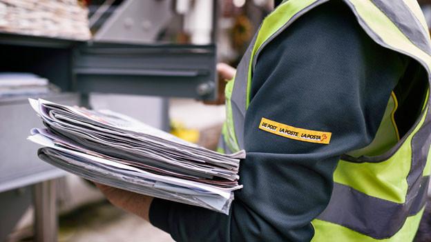 Postangestellte beim Austeilen von Post.