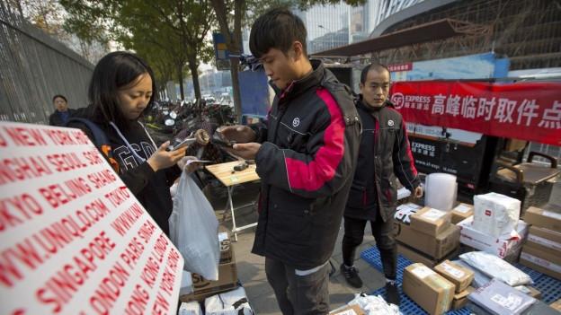 Das Bild zeigt eine Frau in Peking, die ein Päckchen abholt, das sie zuvor im Internet bestellt hatte.