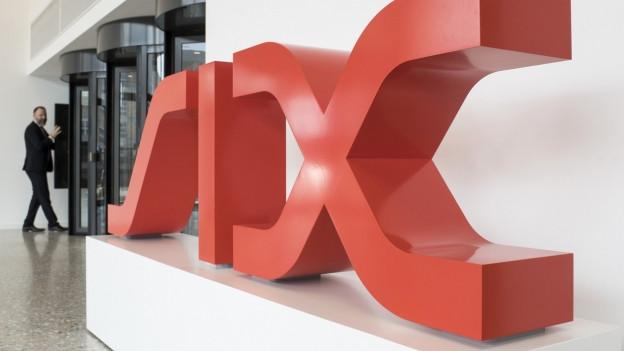 Zu sehen sind Menschen, die sich vor dem Logo der SIX Group in Zürich bewegen.