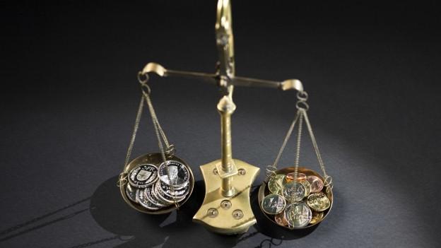 Schweizer Franken auf einer Waage in Balance mit Euromünzen.