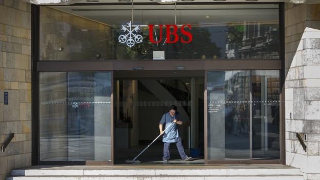 Eine Putzfrau reinigt den Eingangsbereich der UBS-Filiale am Zürcher Paradeplatz.