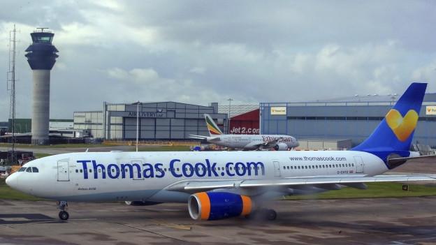 Ein Flugzeug mit dem Schriftzug «Thomas Cook» steht auf einem Flugplatz.