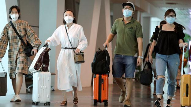 Touristinnen und Touristen am Flughafen von Kuala Lumpur, Malaysia. Symbolbild.