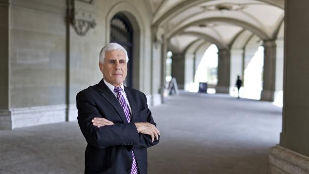 Rudolf Strahm steht vor einem Nebeneingang des Bundeshauses, er hat die Arme vor der Brust verschränkt.