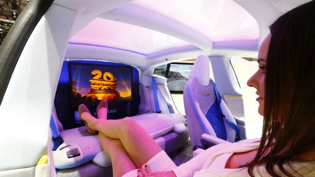 Innenaufnahme eines Prototypen am Genfer Autosalon: Fahrer und Beifahrersitze lassen sich umdrehen, über den Rücksitzen ist ein Bildschirm, auf dem ein Film läuft.