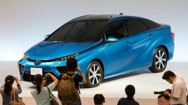 Interessierte fotographieren das neue Auto-Modell von Toyota.