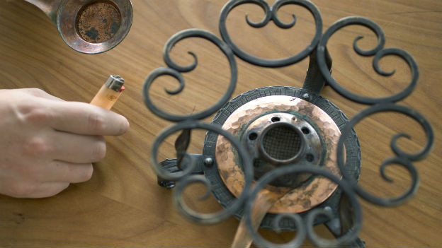 Blick von oben auf einen Tisch mit einem Fondue-Rechaud, das eine Männerhand gerade anzündet.