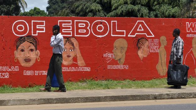 Das Bild zeigt eine orange bemalte Mauer. Auf ihr steht: «Ebola of». Zu sehen sind auch gemalte Köpfe, die die Symptome von Ebola zeigen. Vor der Mauer laufen zwei Fussgänger.