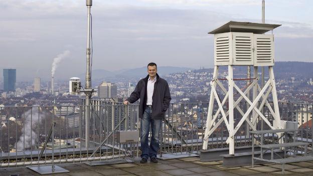 Reto Knutti steht auf dem Dach eines Hochhauses, rechts von ihm steht eine Klima-Messstation.
