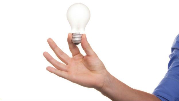 Glühbirne, die von einem männlichen Arm in die Luft gehalten wird. Der Hintergrund ist weiss.