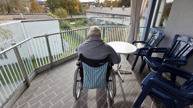 Aufnahme eines alten Mannes im Rollstuhl auf dem Balkon eines Altersheims für Demenzkranke.