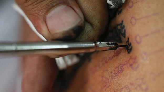 Das Bild zeigt eine Hand mit einer Tattoo-Nadel, die gerade ein schwarzes Tatoo sticht.