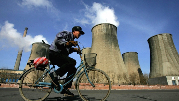 Ein Mann fährt auf einem Velo vor einem Kohlekraftwerk in China vorbei.