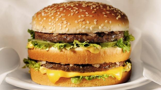 Grossaufnahme eines Doppelburgers, also zwei Scheiben Fleisch, etwas Käse und Salat.