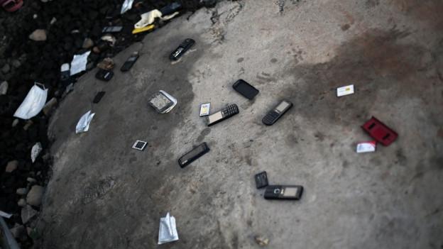 Zerschmetterte Telefone liegen am Boden.