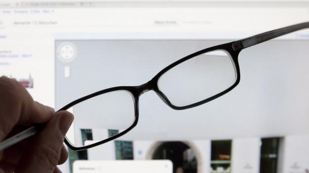 Eine Brille wird vor einen Computer gehalten